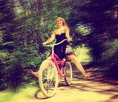 a girl riding a bike on a path in a park full of trees toned with a retro vintage instagram filter
