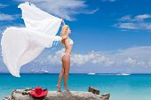 Beautiful young woman in bikini on the beach with pareao on a windy day