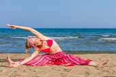 Young woman practicing yoga on the beach