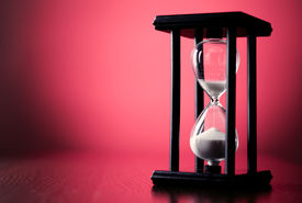 picture of pass-time  - Egg timer or hourglass on a graduated red background with copyspace in a conceptual image of passing time and time management - JPG