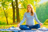 Happy Pregnant Woman Relaxing On The Lawn In The Park