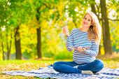 Cheerful Pregnant Woman With A Notebook And Pencil
