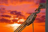 foto of pulley  - hook with pulley under a dramatic sky at sunset - JPG