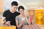 Young Asian couple shopping and looking at cellphone, closeup portrait.