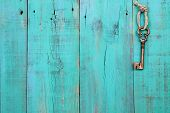 Bronze skeleton key hanging by rope on antique teal blue distressed wood door poster