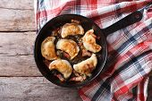 Fried Dumplings With Onion And Bacon In A Pan Horizontal Top View