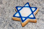 image of star shape  - cookies in the shape of a Star of David white with blue edging lie on the surface the Jewish star