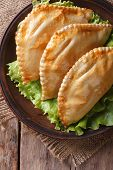 Empanadas On A Plate With Lettuce Close-up. Vertical Top View