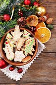 Gingerbread cookies in bowl with Christmas decoration on wooden table background