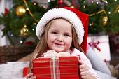 Little girl in Santa hat lying on fur carpet on Christmas tree background