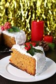 Slice of cake covered cream with Christmas decoration on wooden table and bright background