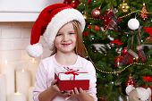Little girl in Santa hat holding present box near Christmas tree on light background