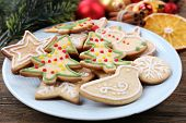 gingerbread cookies on plate with Christmas decoration on wooden table background
