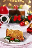 Slice of cake on table with Christmas decoration on bright background