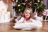 Little girl lying on fur carpet and wooden floor on Christmas tree background