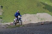 SOCHI, RUSSIA  AUGUST 16, 2014: Off-road motorcycle rider trains in summer mountains