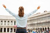 Happy Young Woman Rejoicing On Piazza San Marco In Venice, Italy. Rear View