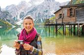 stock photo of south tyrol  - Portrait of young woman with photo camera on lake braies in south tyrol italy - JPG