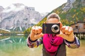 picture of south tyrol  - Closeup on young woman taking photo on lake braies in south tyrol italy - JPG