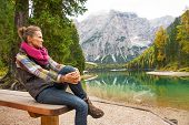 picture of south tyrol  - Young woman sitting while on lake braies in south tyrol italy and looking into distance - JPG