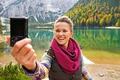 stock photo of south tyrol  - Smiling young woman taking self photo on lake braies in south tyrol italy - JPG