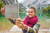 picture of south tyrol  - Happy young woman taking photo with tablet pc while on lake braies in south tyrol italy - JPG