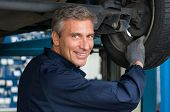Portrait Of Happy Mature Mechanic At Repair Service Station Changing Tire