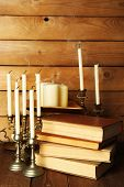 Retro candlesticks with candles and books, on wooden background