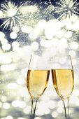 Glasses with champagne over fireworks and sparkling holiday background