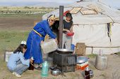 Women cook in front of the yurt in steppe, Mongolia.