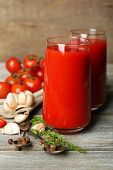 Glasses of tasty tomato juice and fresh tomatoes on wooden table