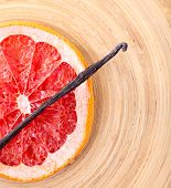 Dried grapefruit with vanilla bean on wooden background