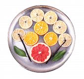Still life of dried citrus with vanilla beans on metal tray isolated on white
