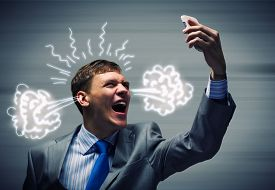 stock photo of screaming  - Angry businessman screaming furiously in mobile phone - JPG