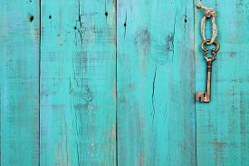 pic of skeleton key  - Brass skeleton key hanging by rope on antique teal blue shabby wood background - JPG