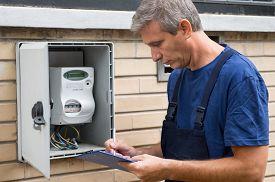 image of electricity meter  - Portrait Of Electrician Worker Inspecting Electric Meter  - JPG