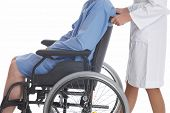 stock photo of rollator  - nurse is pushing her patient on a wheelchair - JPG