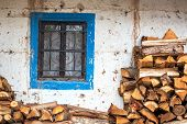 stock photo of firewood  - Firewood next to a blue and white colonial window in Tarma Peru - JPG