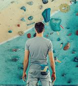 picture of climbing wall  - Young man standing in front of a practical climbing wall indoor and preparing to climb - JPG