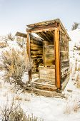 image of forlorn  - Alone in the snow stands this outhouse - JPG