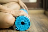 stock photo of yoga mat  - Young woman holding a yoga mat on the floor - JPG