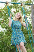 picture of swing  - Blonde student girl in azure blue silk sundress is standing on handmade swing - JPG