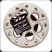 picture of mm  - Original old big movie reel for 35 mm cinema projector loaded with film with clapper board on neutral background vintage color effect - JPG