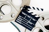 stock photo of mm  - Two movie reels for 35 mm film projector with clapper board and filmstrip on neutral background - JPG