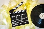 foto of mm  - Empty yellow 35 mm film unrolled with clapper board and cinema movie reel on neutral background - JPG