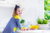 pic of little young child children girl toddler  - Little girl preparing breakfast in white kitchen. Healthy food for children. Child drinking milk and eating fruit. Happy smiling preschooler kid enjoying morning meal cereal banana and strawberry. ** Note: Shallow depth of field - JPG
