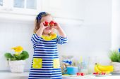 foto of little young child children girl toddler  - Little girl preparing breakfast in white kitchen. Healthy food for children. Child drinking milk and eating fruit. Happy smiling preschooler kid enjoying morning meal cereal banana and strawberry. ** Note: Shallow depth of field - JPG