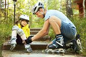 foto of skate  - portrait of a sports dad and daughter in a helmet. Dad with his little daughter on the skates ** Note: Shallow depth of field - JPG