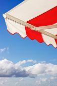 picture of awning  - Red and white Awning over bright blue sky - JPG