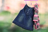 image of habilis  - Fashion baby dresses hanging on a hanger on a green background - JPG